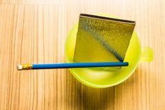 Голубые карандаш и тетрадь в чашке Стоковые Изображения