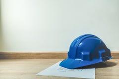 Голубые каски безопасности и домашний план строительства, архитектура или конструкция или промышленные оборудования, с космосом э Стоковая Фотография RF