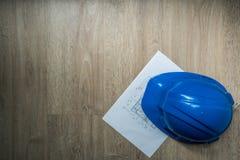 Голубые каски безопасности и домашний план строительства в темном абстрактном тоне, архитектуре или промышленных оборудованиях, с Стоковое фото RF