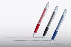 Голубые, красные и черные ручки на белой предпосылке Стоковая Фотография