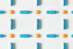 Голубые медицинские пилюльки и картина капсул на белой предпосылке Плоское положение, взгляд сверху Стоковое Изображение