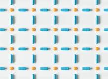 Голубые медицинские пилюльки и картина капсул на белой предпосылке Плоское положение, взгляд сверху Стоковые Изображения
