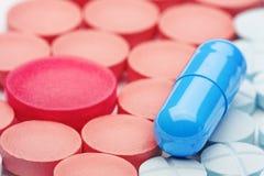 Голубые медицинские пилюльки на предпосылке голубых и красных пилюлек Стоковые Фото