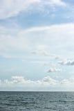 Голубые море и облака на небе Стоковые Изображения