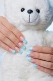Голубые ногти на белой мягкой игрушке Стоковые Изображения RF