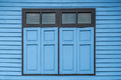 Голубые окна на старой деревянной стене Стоковые Фото