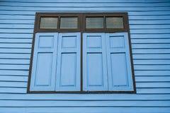 Голубые окна на старой деревянной стене Стоковое Изображение