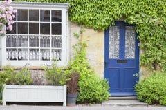 Голубые парадные входы в старом доме окруженном зелеными растениями Стоковая Фотография