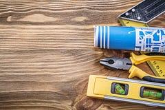 Голубые плоскогубцы правителя квадрата уровня плана строительства на деревянной доске Стоковые Фотографии RF
