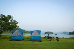 Голубые располагаясь лагерем шатры и велосипед 2 на береге в утре Стоковое Фото