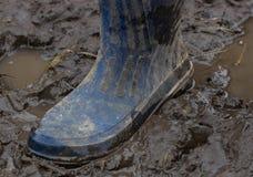 Голубые резиновые ботинки в грязи после дождя Конец-вверх Стоковая Фотография
