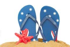 Голубые сандалии и морские звёзды в песке Стоковая Фотография
