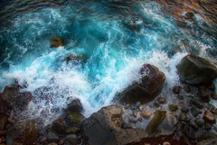 Голубые свирепствуя волны разбивая на утесах стоковое изображение rf
