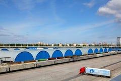 Голубые склады ангаров, выровнянные в ряд, немного зданий. Стоковые Фото