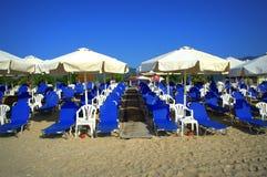 Голубые sunbeds на песчаном пляже Стоковые Фото