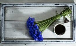 Голубые wildflowers с чашкой кофе в старой рамке Стоковые Фото