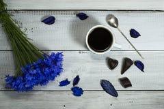Голубые wildflowers с чашкой кофе и конфетами Стоковое Фото