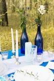 2 голубых бутылки такая ваза с цветками на таблице банкета украшение Стоковое Изображение RF