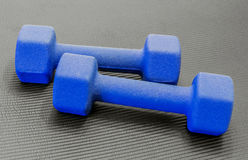 2 голубых гантели лежа на открытой черной циновке йоги тренировки Стоковые Фото