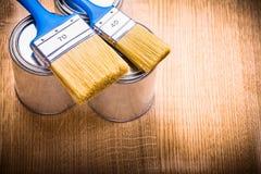 2 голубых кисти на чонсервных банках и деревянной доске Стоковые Фотографии RF