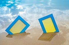 2 голубых пустых рамки фото на песке приставают к берегу Стоковые Изображения