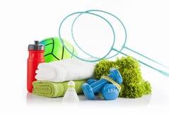 2 голубых ракетки бадминтона полагаясь против кучи белых и зеленых полотенец с красной бутылкой с водой велосипеда и зеленой рези Стоковое Изображение