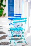 2 голубых стуль на улице типичной греческой традиционной деревни на острове Mykonos, Греции, Европе Стоковое Изображение RF
