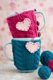 2 голубых чашки в голубом и розовом свитере с сердцами войлока Стоковые Фотографии RF