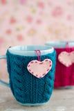 2 голубых чашки в голубом и розовом свитере с сердцами войлока Стоковое Фото