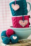 2 голубых чашки в голубом и розовом свитере с сердцами войлока Стоковые Фото