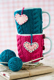 2 голубых чашки в голубом и розовом свитере с сердцами войлока Стоковые Изображения