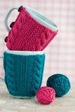 2 голубых чашки в голубом и розовом свитере с шариком пряжи Стоковые Изображения