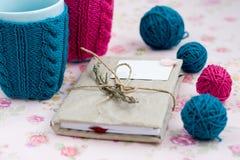 2 голубых чашки в голубом и розовом свитере с шариком для вязать Стоковое Изображение