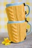2 голубых чашки в желтом свитере и желтом цветке Стоковая Фотография