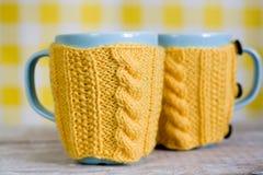 2 голубых чашки в желтом свитере на ткани Стоковое Фото