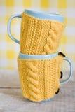 2 голубых чашки в желтом свитере Стоковые Изображения