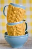2 голубых чашки в свитере на предпосылке ткани Стоковые Изображения