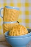 2 голубых чашки в свитере на предпосылке ткани Стоковое Изображение