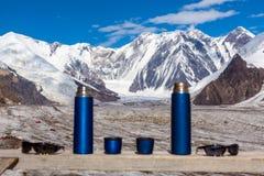 2 голубых чашки и солнечного очк Thermoses перемещения на деревянном ландшафте таблицы и горы Стоковое Изображение