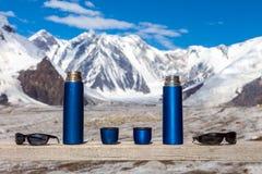2 голубых чашки и солнечного очк Thermoses перемещения на деревянном ландшафте таблицы и горы Стоковые Изображения