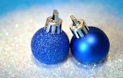 2 голубых шарика рождества на белом ярком блеске на голубой предпосылке Стоковые Фото