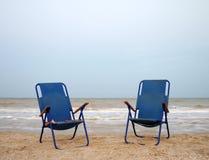 2 голубых шезлонга на песке около моря Стоковое Изображение RF