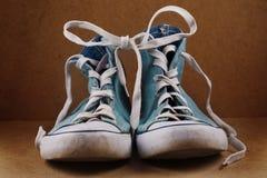 2 голубых шнурка ботинка соединили на коричневой предпосылке Стоковые Изображения