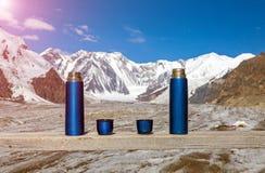 2 голубых Thermoses и чашки на деревянном столе с горами на предпосылке и светя Солнце Стоковые Изображения