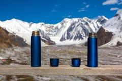 2 голубых Thermoses и чашки на деревянном столе с красивыми горами Гималаев на предпосылке Стоковое Изображение RF