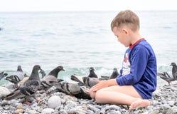 Голубь мужского ребенк подавая на пляже используя руку Стоковая Фотография