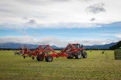 Грабл сена прикрепленная к красному трактору работает на ферме делая сено стоковые фотографии rf