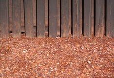 Гравий задавленный красным цветом с деревянной стеной стоковые фото
