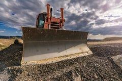 Гравий экскаватора двигая на строительной площадке стоковое фото rf