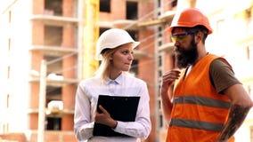 2 гражданского инженера держа планы и проверяя строительную площадку Мужчина и женский построитель в защитных шлемах сток-видео